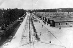 KL Dachau: general view of the prisoner barracks, high-voltage barbed-wire fence electrified at all times, KL Dachau prisoners next to the barracks. /April 1945/. (IPN)