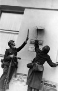 German soldiers removing the Polish national emblem from one of the offices in Gdynia, September 1939 (BArch)